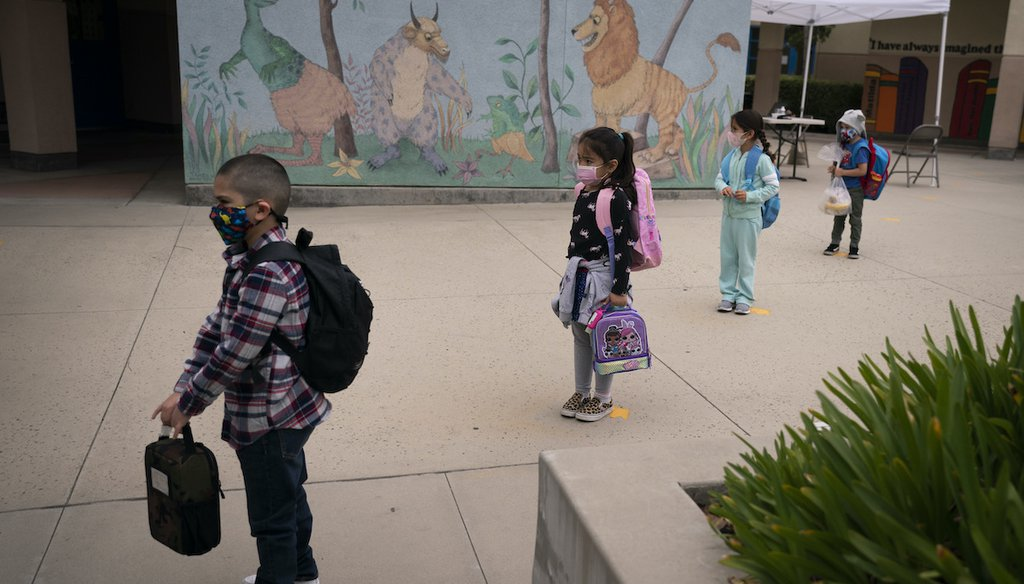Socially distanced kindergarten students wait for their parents to pick them up on the first day of in-person learning at Maurice Sendak Elementary School in Los Angeles, Tuesday, April 13, 2021. (AP)