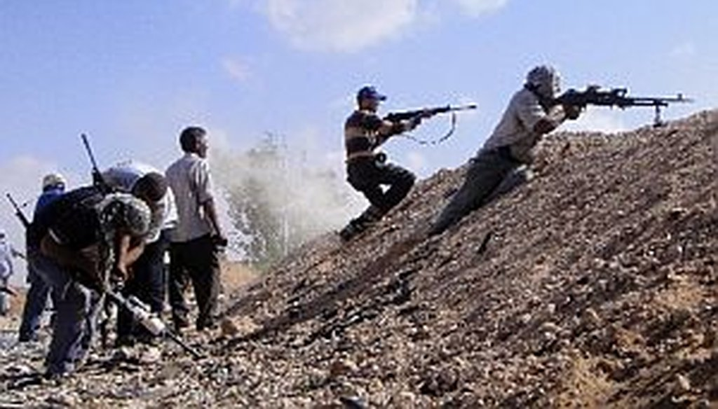 Libyan rebel fighters fire their machine guns towards pro-Gadhafi forces. The U.S. and NATO are enforcing a no-fly zone.