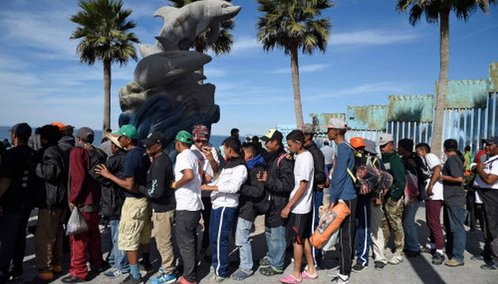 Central American migrants moving towards the United States in hopes of a better life, queue for pizza Nov. 15, 2018, near the U.S.-Mexico border fence in Playas de Tijuana, Mexico (Getty Images).