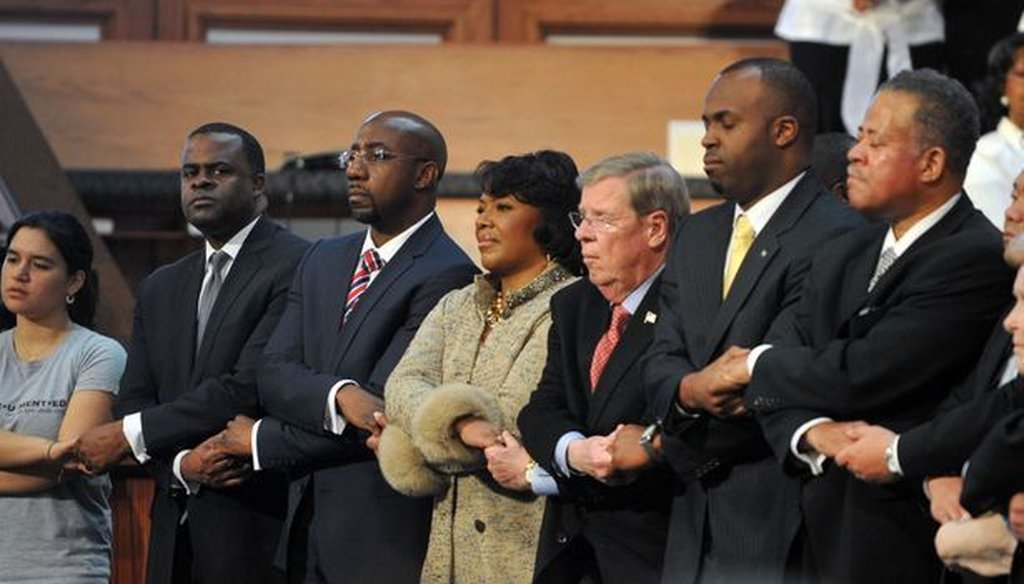 """The Rev. Raphael Warnock, third from the left, and other speakers hold hands while singing """"We Shall Overcome"""" at the conclusion of the Martin Luther King Jr. commemorative service. Photo credit: Kent Johnson/AJC."""