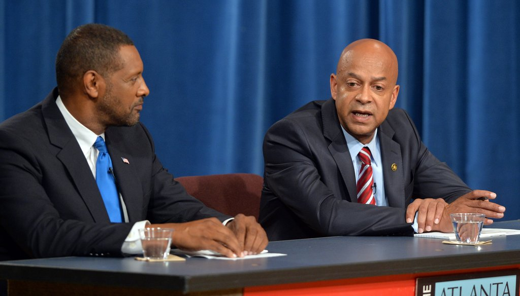 Jeff Mann, left, makes a point during the recent APC debate