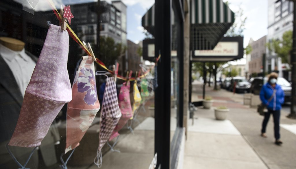 A person wearing a protective face mask as a precaution against the coronavirus walks by a shop displaying face coverings in Allentown, Pa., Tuesday, May 12, 2020. (AP Photo/Matt Rourke)