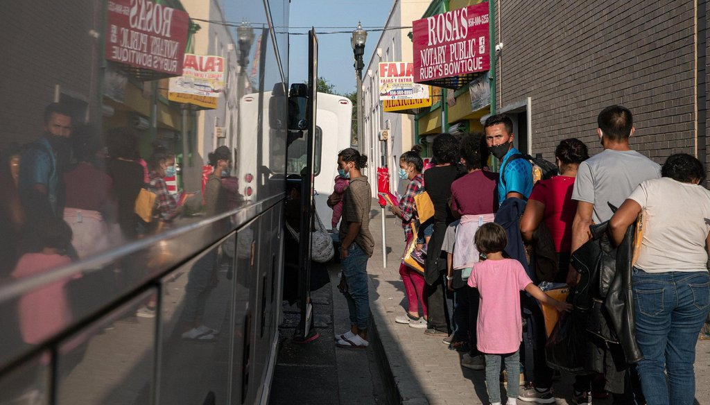 A group of migrants wait to board a charter bus in front of the Catholic Charities RGV Humanitarian Respite Center in McAllen on Tuesday, July 27, 2021.