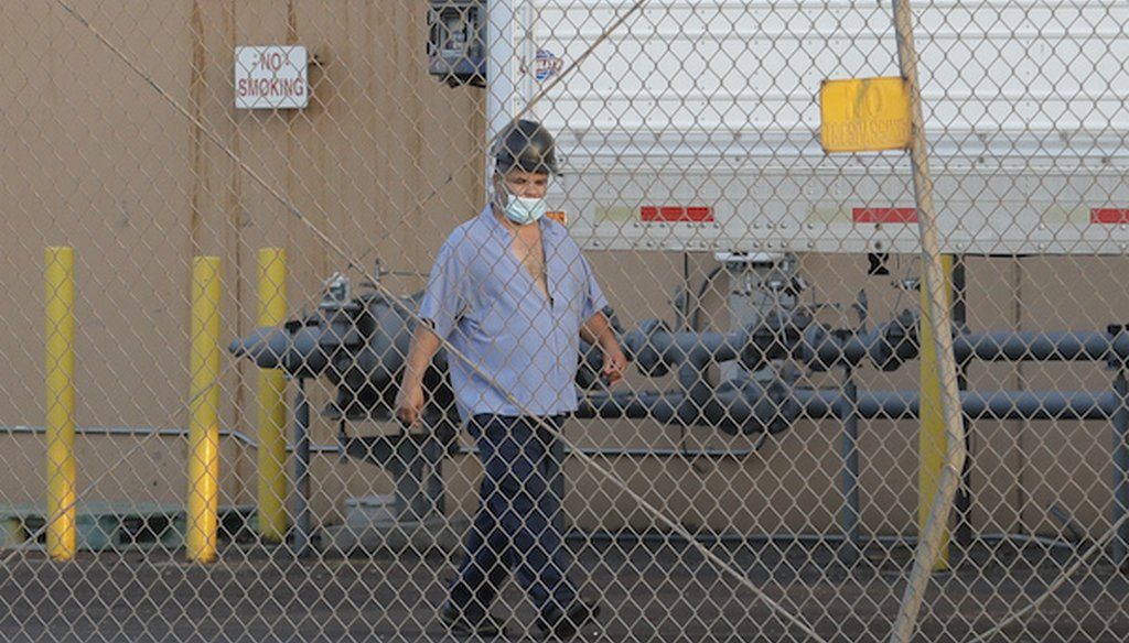 A worker wears a mask as he walks behind a fence at Agri Beef's Washington Beef processing plant in Toppenish, Wash., on May 7, 2020. (AP)