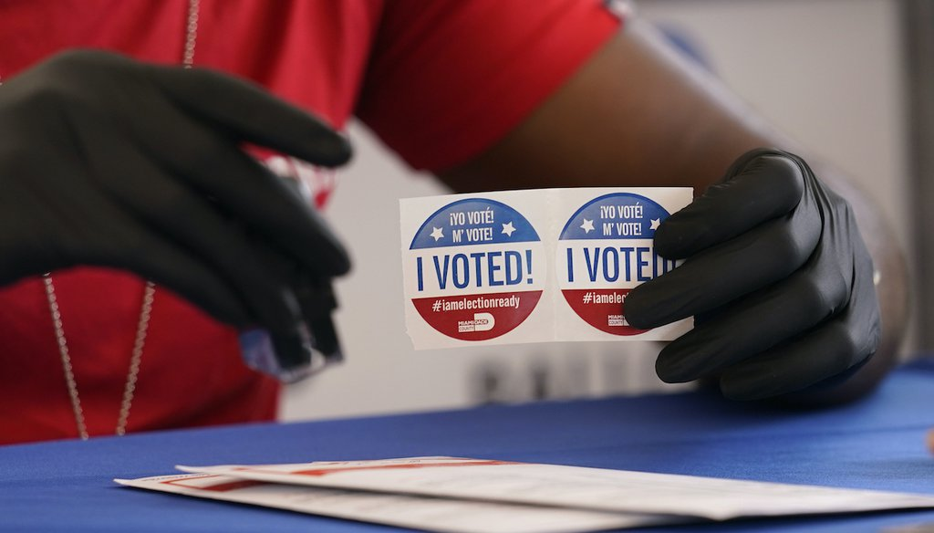 """An election worker holds """"I Voted"""" stickers as people drop off vote-by-mail ballots for the Nov. 3 general election at the Miami-Dade County Elections Department, Wednesday, Oct. 14, 2020, in Doral, Fla. (AP)"""