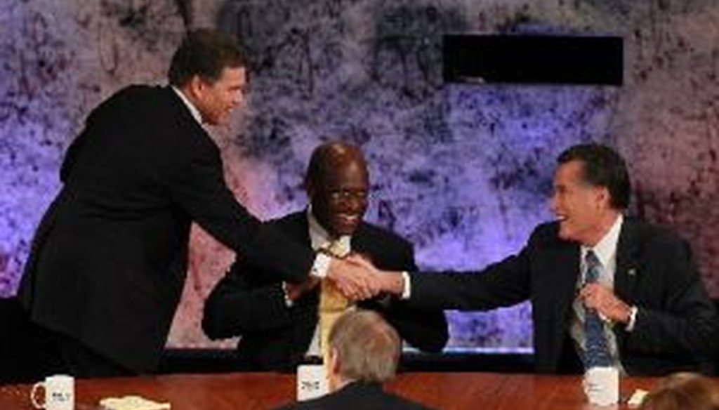 As Herman Cain looks on, Rick Perry and Mitt Romney shake hands at the conclusion of the Republican Presidential debate at Dartmouth College in Hanover, N.H.