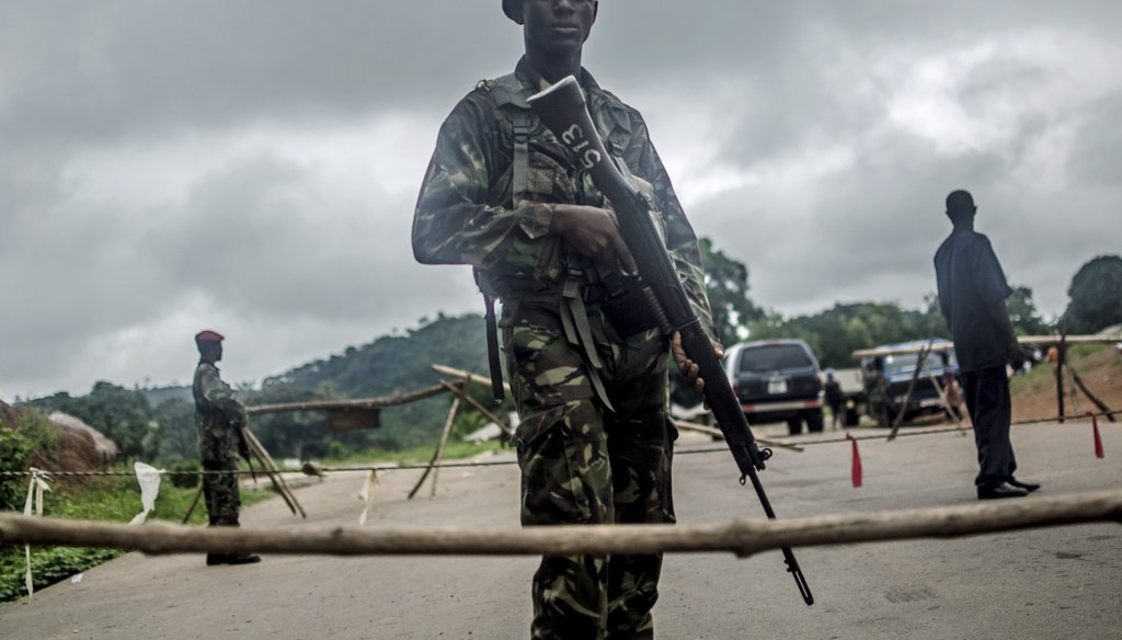 Soldiers stand guard at a roadblock outside Kenema, Sierra Leone, Aug. 8, 2014. (New York Times)