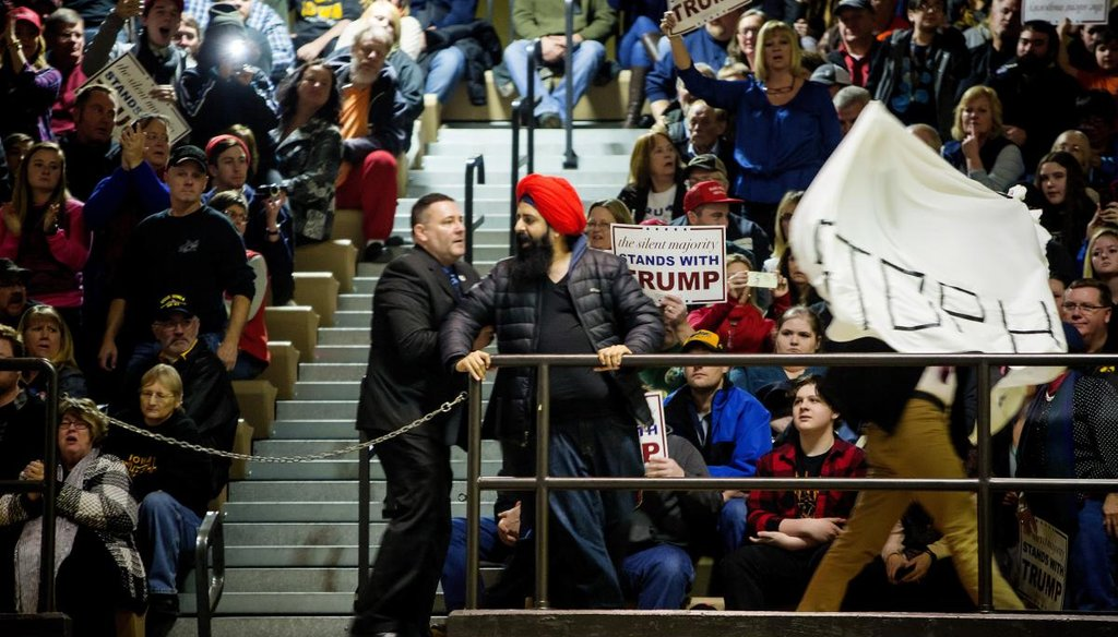 Two protesters are escorted from an event for Donald Trump at Muscatine High School in Muscatine, Iowa, Jan. 24, 2016. (Eric Thayer/The New York Times)