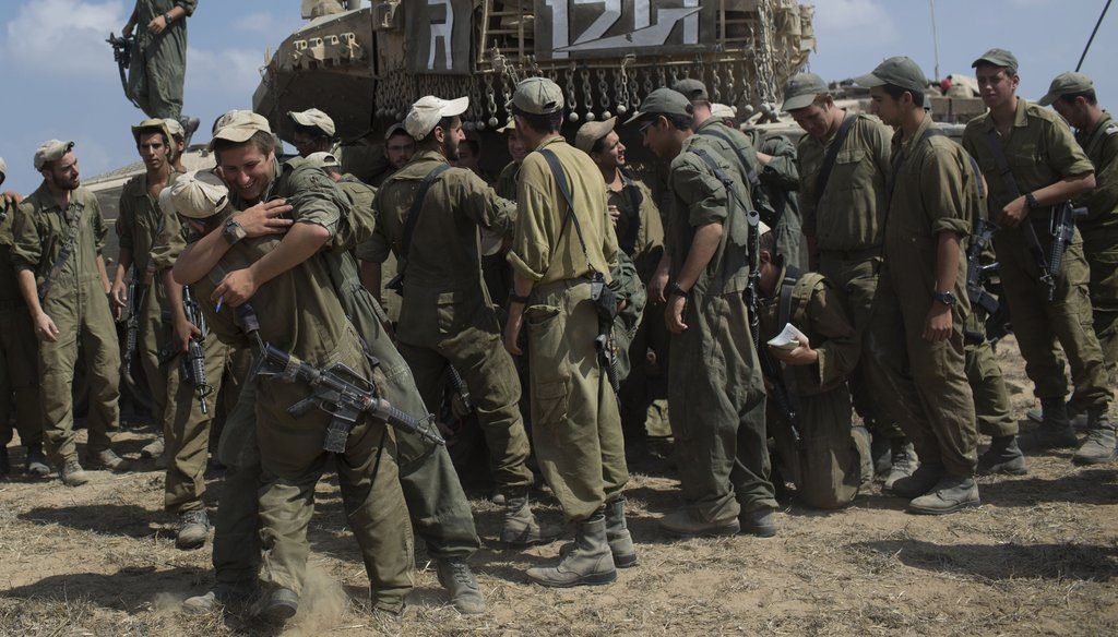Israeli soldiers embrace as they prepare to leave the country's border with Gaza, Aug. 5, 2014. (New York Times)