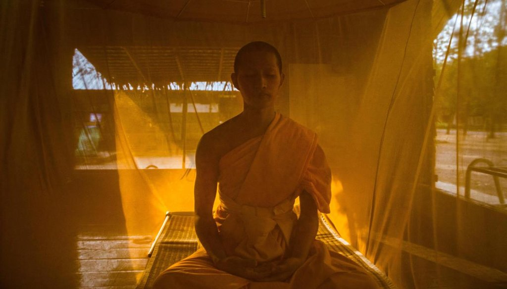 A novice monk takes part in evening meditation, under his mosquito net, in the monastery within Wat Dhammakaya in Bangkok, Dec. 12, 2016. (Lauren DeCicca/The New York Times)