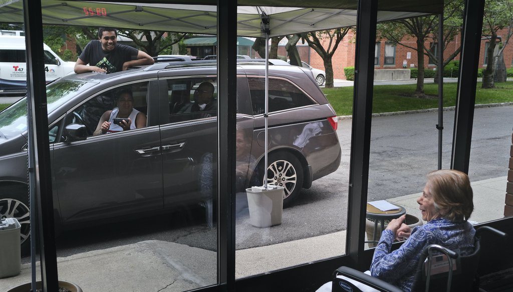 Gloria DeSoto, 92, right, visits with her family, in their car, from a window of the Hebrew Home at Riverdale, where she lives, in New York, Thursday, June 11, 2020. (AP)