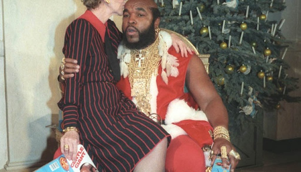 First Lady Nancy Reagan sits on the knee of television personality Mr. T, dressed as Santa Claus in 1983. (Wikipedia photo)