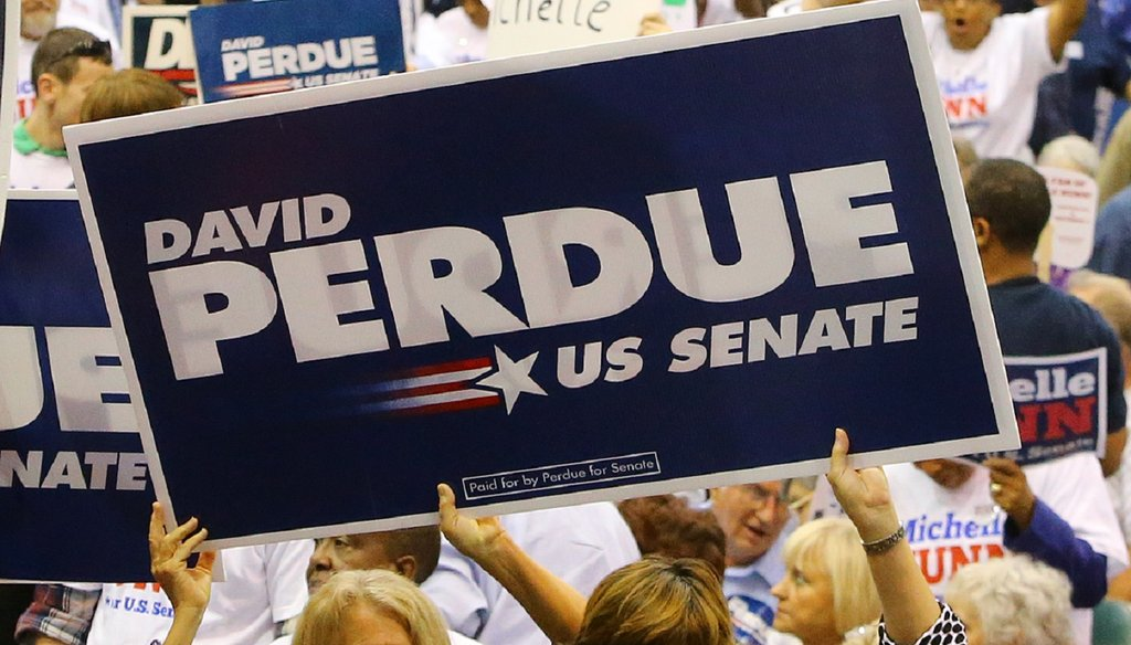 Supporters of David Perdue and Michelle Nunn wave signs just before the U.S. Senate debate at the Georgia National Fair on Oct. 7. Photo by Curtis Comptom/AJC.