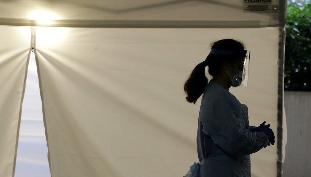 A nurse stands outside a drive-up coronavirus testing station at the University of Washington Medical Center. (AP Photo/Ted S. Warren)