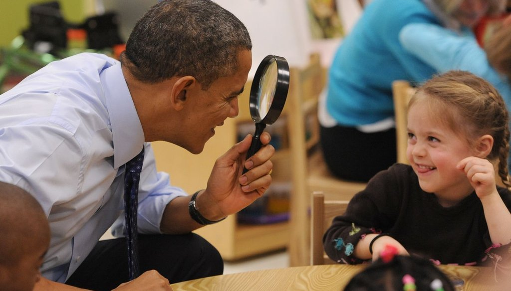 President Barack Obama playfully peers through a magnifying lens at a child while visiting an early care center in Decatur, Ga. Obama wants to devote more federal resources to programs like these.