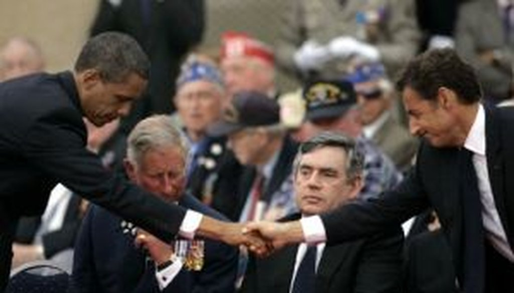 President Barack Obama, left, shakes hands with French President Nicolas Sarkozy, as Britain's Prince Charles and Prime Minister Gordon Brown look on during the 65th anniversary of D-Day in Normandy.