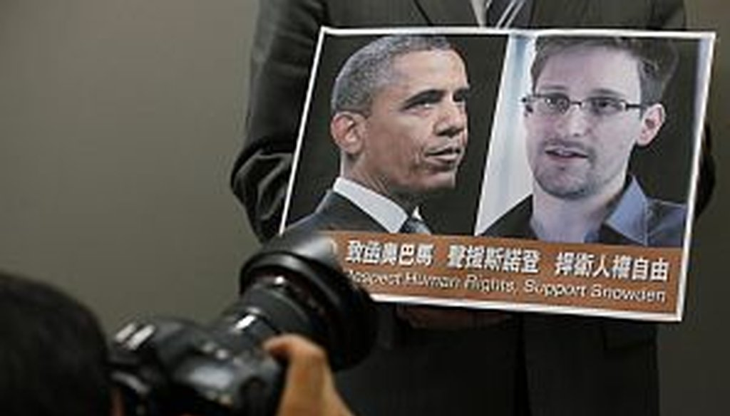 A protestor holds a sign supporting Edward Snowden at a June news conference in Hong Kong. (AP Photo)