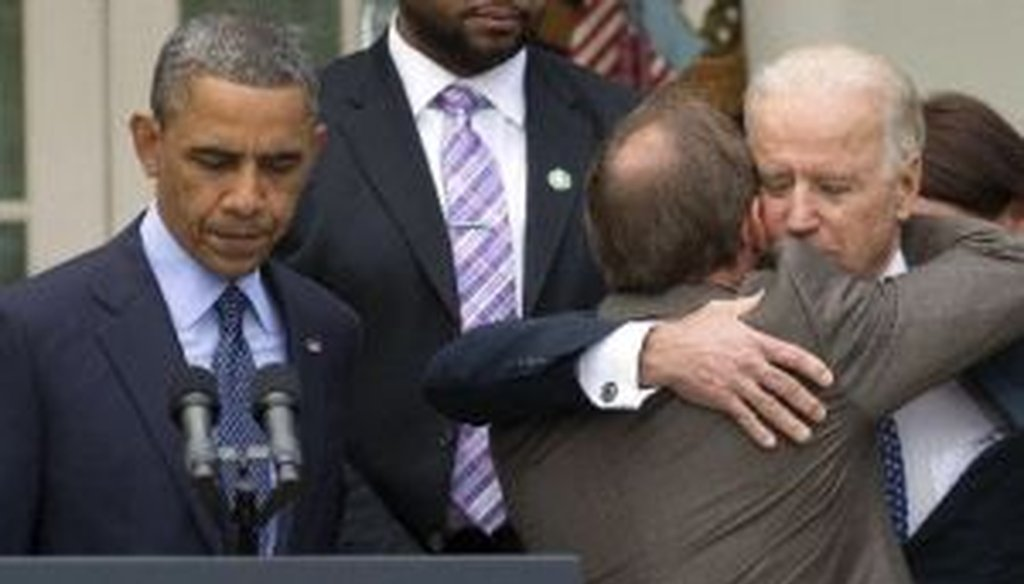 President Barack Obama stands at the podium as Mark Barden, father of a Newtown shooting victim, is embraced by Vice President Joe Biden during a Rose Garden news conference on gun policy.