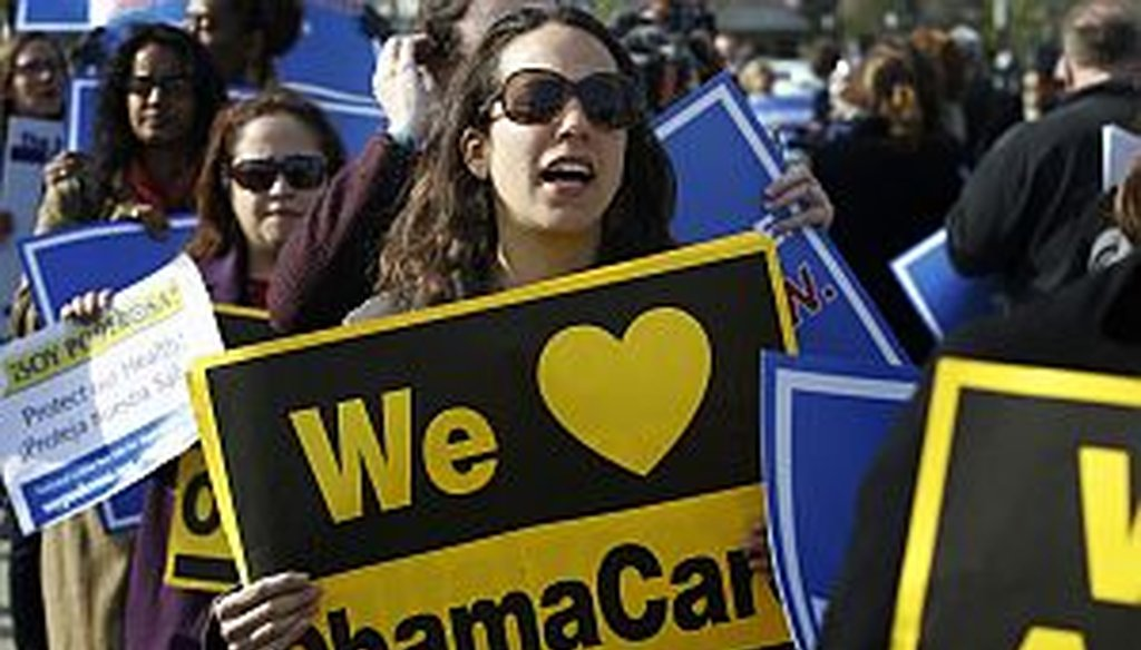 Supporters of health care reform stand in front of the Supreme Court in Washington on March 28, 2012. (AP Photo)