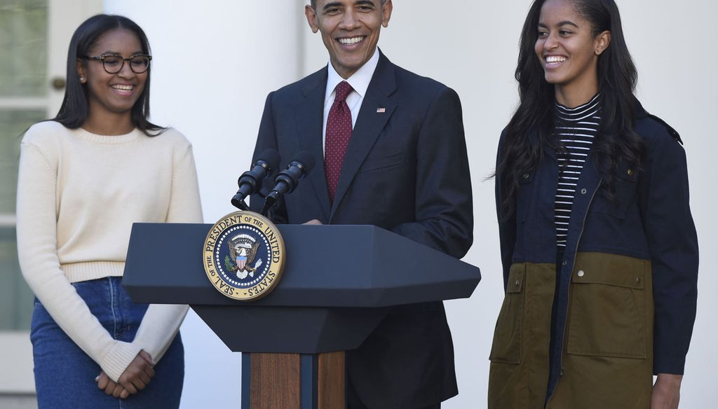 President Barack Obama standing with his daughters, Sasha, left, and Malia, right, as Obama pardons a turkey at the White House on Nov. 25, 2015. (AP)