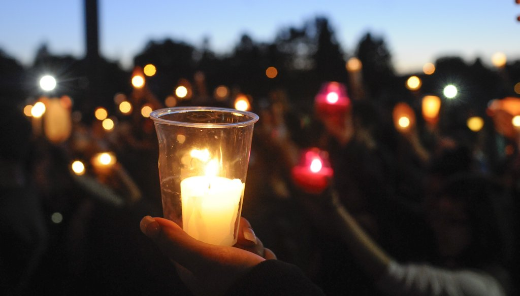 Students, faculty and parents gather for a candlelight vigil to remember a Reynolds High School student shot and killed at the school Tuesday morning. The shooter, also a Reynolds student, took his own life.