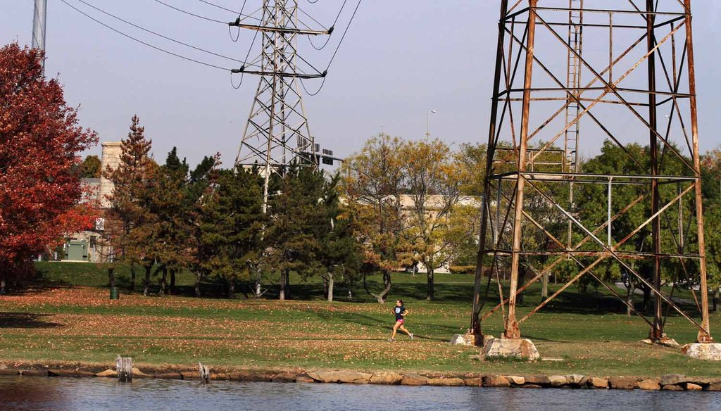A runner is dwarfed by towers carrying power lines over India Point Park in Providence, RI. (The Providence Journal / Andrew Dickerman)