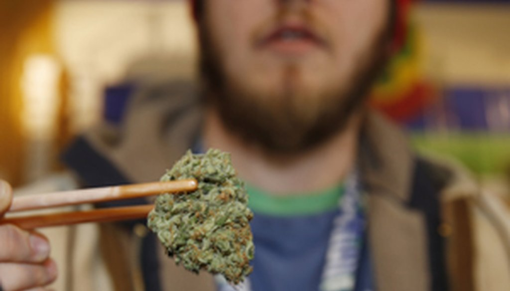 Sales associate Matt Hart uses chopsticks to hold a bud of Lemon Skunk, the strain of highest potency available at the 3D Dispensary, in Denver. (AP / David Zalubowski)