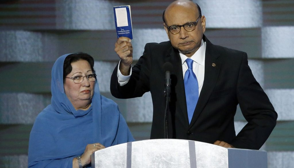 Khizr Khan holds a copy of Constitution of the United States, that he offered to lend to Donald Trump, with his wife Ghazala Khan, during the last day of the Democratic National Convention. (TNS)