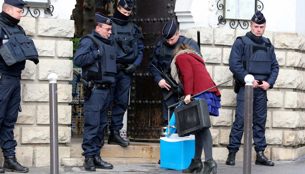 Riot police officers check a woman at the Grand Mosque of Paris, France, Wednesday, Jan. 14, 2015, the day the French satirical newspaper Charlie Hebdo released its first issue after a lethal terrorist attack, (AP)