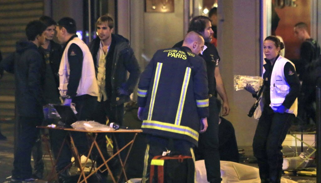 Rescue workers at the scene as victims lay on the pavement outside a Paris restaurant on Nov. 13, 2015. (AP photo)