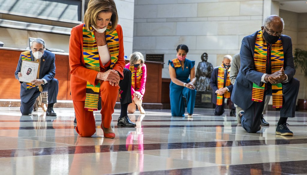House Speaker Nancy Pelosi of Calif., center, and other members of Congress, kneel and observe a moment of silence at the Capitol's Emancipation Hall. (AP Photo/Manuel Balce Ceneta)