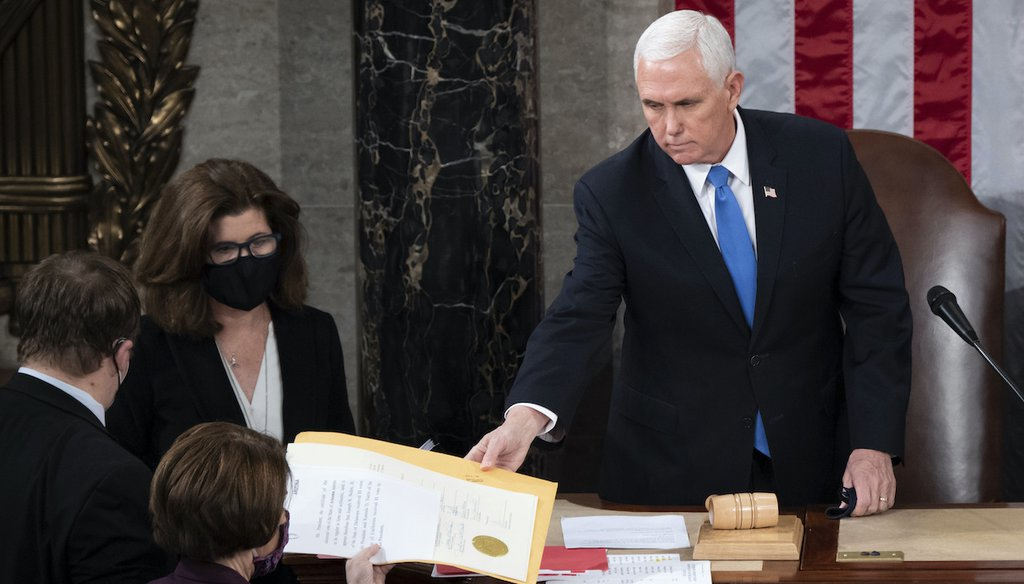 Vice President Mike Pence hands the electoral certificate from the state of Arizona to Sen. Amy Klobuchar, D-Minn., as he presides over a joint session of Congress as it convenes to count the Electoral College votes on Jan. 6, 2021. (AP)