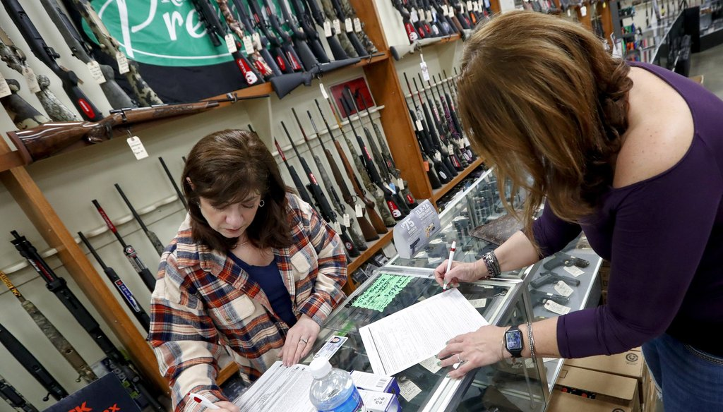 Andrea Schry, right, fills out the buyer part of legal forms to buy a handgun as shop worker Missy Morosky fills out the rest at Dukes Sport Shop in New Castle, Pa. (AP Photo/Keith Srakocic)