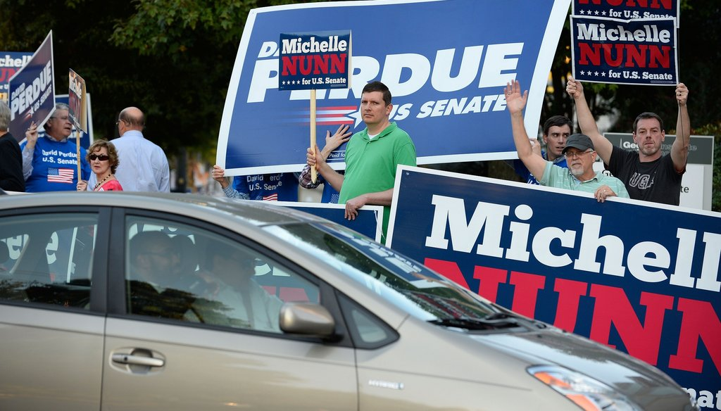 Supporters of U.S. Senate candidates Democrat Michelle Nunn and Republican David Perdue wave signs before before a debate in Atlanta on Oct. 26. David Tulis / AJC Special