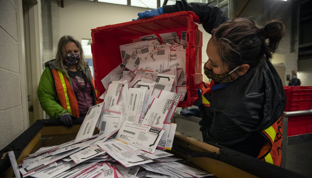 Election worker Kristen Mun from Portland empties ballots from a ballot box at the Multnomah County Elections Division, Tuesday, Nov. 3, 3030 in Portland, Ore. (AP)