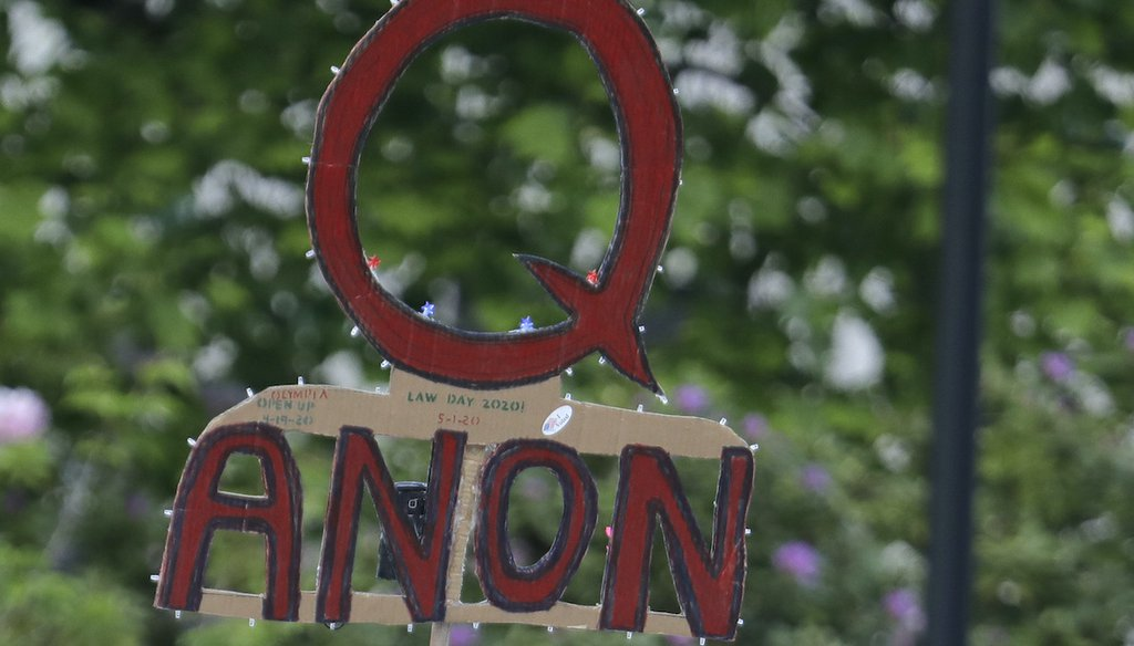 A sign supporting QAnon is hoisted at a May 14, 2020, protest rally in Olympia, Wash. (AP)