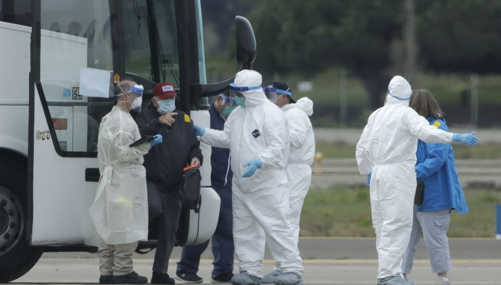 Passengers from the Grand Princess, a cruise ship carrying multiple people who have tested positive for COVID-19, exit a bus before boarding a chartered plane in Oakland, Calif., on March 10, 2020. (AP)