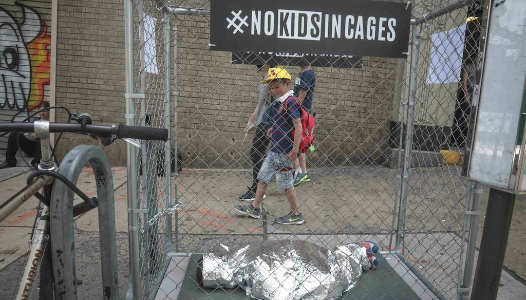 Riders leaving a subway station in Brooklyn, N.Y., pass by a pop-up art installation on June 12, 2019. The project featured mannequins as part of the #NOKIDSINCAGES campaign to support Refugee and Immigrant Center for Education and Legal Services. (AP)