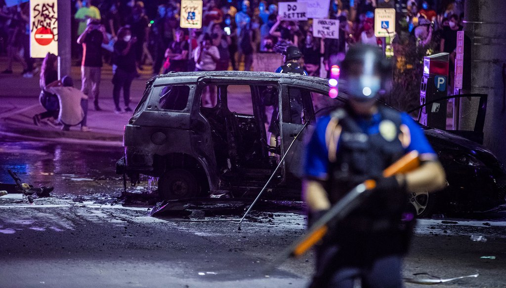 PD stand guard as Austin Fire Department put out a car fire under Interstate 35 freeway in Austin Texas. Demonstrators protest over the police killing of George Floyd Saturday, May 30, 2020.[RICARDO B. BRAZZIELL/AMERICAN-STATESMAN]