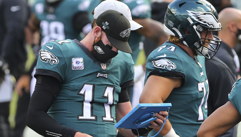 Philadelphia Eagles' Carson Wentz wears a mask as he looks at his Microsoft tablet during an NFL football game, against the Baltimore Ravens, Sunday, Oct. 18, 2020, in Philadelphia. (AP Photo/Rich Schultz)