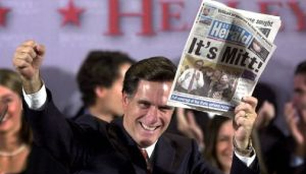 Mitt Romney displays a newspaper declaring his victory in the Massachusetts governors race on Nov. 5, 2002. As a presidential candidate in 2012, he touted his fiscal record as governor.