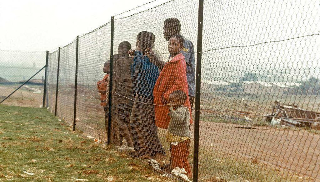 Children stand behind a fence that separates them from the white community near Johannesburg in 1973 (UN Photo)