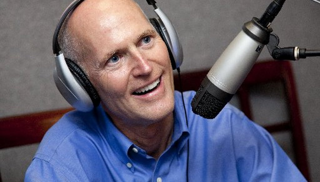 We couldn't find a picture of Florida Gov. Rick Scott reading a newspaper. Here he is during a radio interview.
