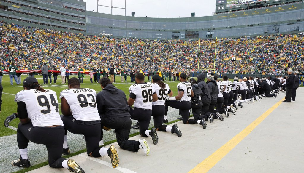 New Orleans Saints players kneel briefly before the national anthem, then stand and lock arms during the anthem, prior to their game against the Green Bay Packers at Lambeau Field in Green Bay, Wis., on Oct. 22, 2017. (Jeffrey Phelps/Associated Press)