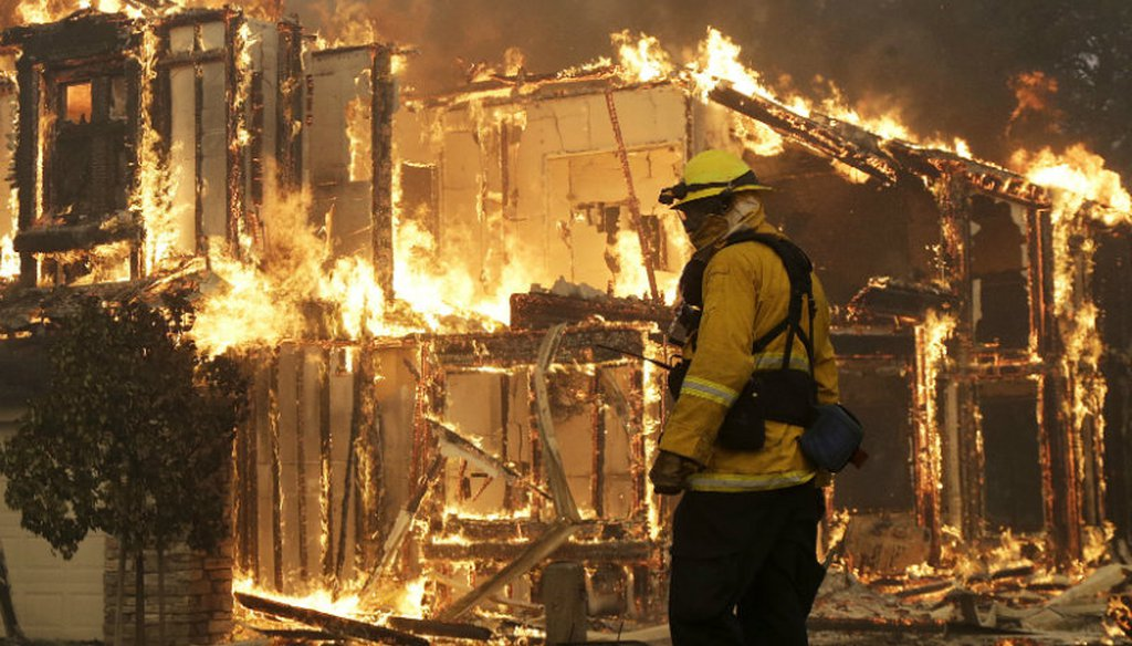 A firefighter monitors a house burning in Santa Rosa, Calif., Monday, Oct. 9, 2017. Wildfires whipped by powerful winds swept through Northern California causing residents to flee to safety through smoke and flames as homes burned. (AP Photo/Jeff Chiu)