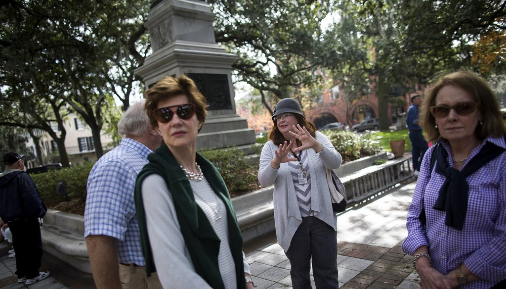 Tourists listen to a guide describe the history at Savannah's Madison Squre. Photo by the New York Times