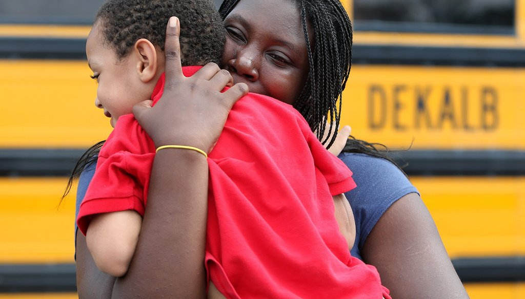 LaTrease Akins rushes off hugging her 5-year-old son Mark Wheeler after being reunited following the shooting incident at McNair Discovery Learning Academy in August 2013. Photo by Ben Gray/AJC