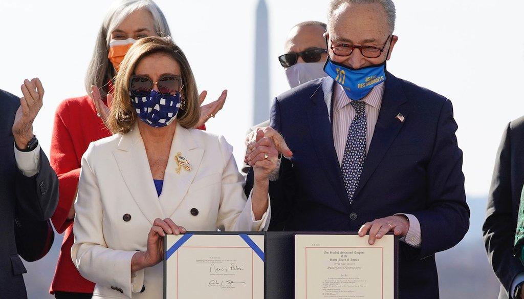 House Speaker Nancy Pelosi of Calif., and Senate Majority Leader Chuck Schumer talk after signing the $1.9 trillion COVID-19 relief bill. (AP Photo/Alex Brandon)