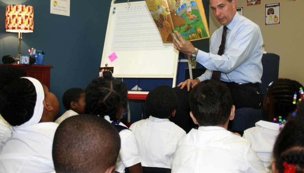 Gov. Scott Walker, shown here reading to first-graders at a private school in Milwaukee in September 2014, made historic cuts to public education funding but later restored some of the money.