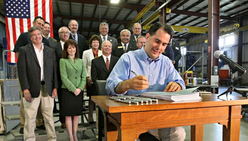 Wisconsin Gov. Scott Walker signed his first state budget, for 2011-'13, at a manufacturing facility. (Michael Sears/Milwaukee Journal Sentinel)